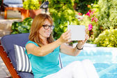 Lady sitting at garden taking selfie — Stock Photo