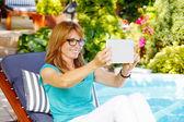 Lady sitting at garden taking selfie — Stock Photo