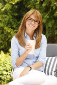 Business woman with mug relaxing a — Stockfoto