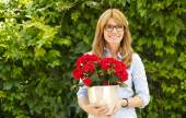 Middle age woman with flower pot — Stock Photo