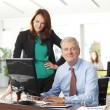 Businesswoman and businessman working on laptop — Stock Photo #55988355