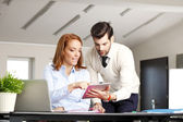 Businessman with tablet discussing with businesswoman — Stock Photo