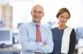 Businesswoman and businessman standing at office — Stock Photo