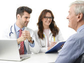Medical team with elderly patient. — Stock Photo
