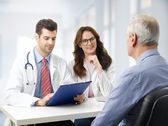 Medical team with elderly patient — Stock Photo