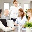 Business people sitting around conference table — Stock Photo #68984277