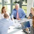Businessmen shake hands across a table — Stock Photo #70206617