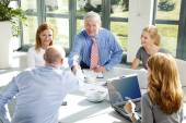 Businessmen shake hands across a table — Stock Photo