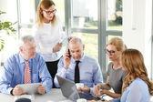 Businesswomen and businessmen sitting at desk — Stock Photo