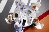 Business people sitting around desk — Stock Photo