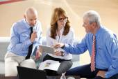Businesswoman holding tablet at office with businessmen — Stock Photo