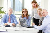 Businesswomen and businessmen working at laptop — Stock Photo
