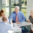 Business team sitting around conference table — Stock Photo #73271023