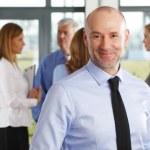 Senior businessman standing at office — Stock Photo #73273713