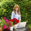 Woman with laptop at flower shop — Stock Photo #73275967