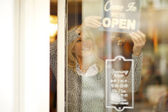 Woman behind her clothing store window — Stock Photo