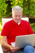 Man at garden and using laptop — Stock Photo