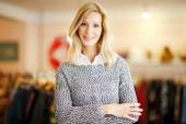 Clothing store owner with arms crossed — Stock Photo