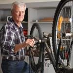 Senior man repairing bike — Stock Photo #75382803