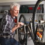 Senior man repairing bike — Stock Photo #75382793