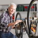 Senior man repairing bike — Stock Photo #75382843
