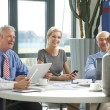 Business team sitting around at conference table — Stock Photo #75385087