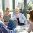 Business team sitting around at conference table — Stock Photo #75385101