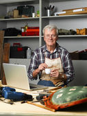 Carpenter sitting  in front of laptop — Stock Photo