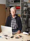 Retired man sitting in front of laptop — Stock Photo