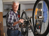 Senior man repairing bike — Stock Photo