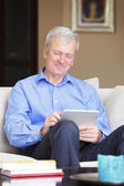 Man sitting at sofa with tablet — Stock Photo