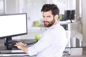 Casual businessman sitting at desk — Stock Photo