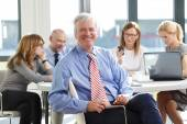 Senior businessman sitting at business meeting — Stock Photo