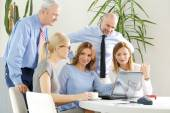 Businesswomen and businessmen around conference table — Stock Photo