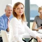 Smiling businesswoman sitting at meeting — Stock Photo #76595005