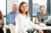 Smiling businesswoman sitting at meeting — Stock Photo