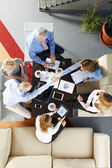 Business team sitting around desk — Stock Photo
