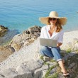 Casual female working by seaside — Stock Photo #78926716