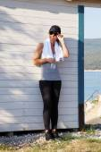 Fit female standing at seaside after running — Stock Photo