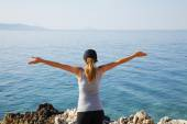 Fit woman standing with arms raised by sea — Stock Photo