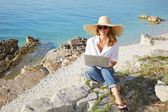 Casual female working by seaside — Stock Photo