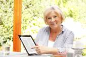 Retired woman at garden using ebook reader — Stock Photo