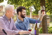 Young and senior men tasting red wine — Stock Photo