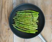 Green asparagus is cooked in frying pan — Stock Photo