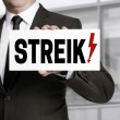 Businessman holding strike sign to viewer — Stock Photo #72494755