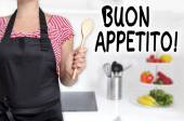 Buon appetito cook holding wooden spoon background — Stock Photo