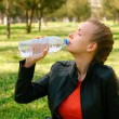 Beautiful young woman wearing drinking water in green park. — Stock Photo #69511361
