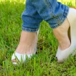 Female feet in shoes with wedge heels on green grass — Stock Photo #70473963