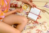 Woman sitting on the bed, drinking coffee and reading book — Stockfoto