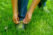 Man tying his shoelaces on his sneakers green grass — Stock Photo